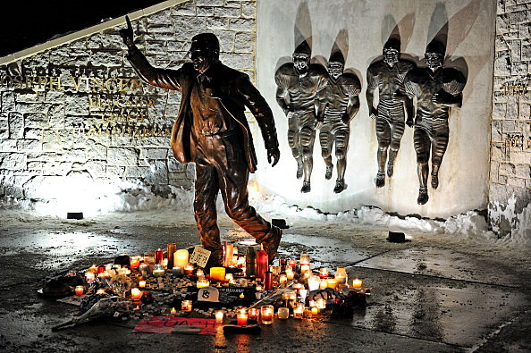 Candles, many burnt out, circle the statue of Joe Paterno