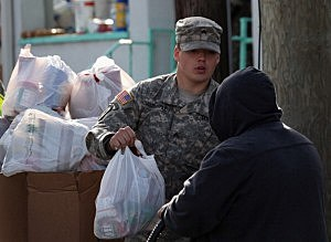 A US Army soldier distributes goods to needy and displaced residents in Far Rockaway, Queens