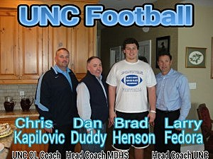 (L-R) UNC offensive line coach Chris Kapilovic, Monsignor Donovan head coach Dan Duddy, Brad Henson and UNC head coach Larry Fedora