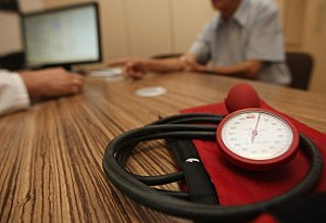 A doctor speaks to a patient as a sphygmomanometer, or blood pressure meter, lies on his desk