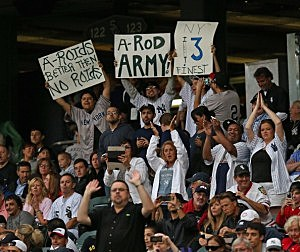 Fans of the New York Yankees cheer and hold signs as Alex Rodriguez steps uo to bat against the Chicago White Sox at U.S. Cellular Field