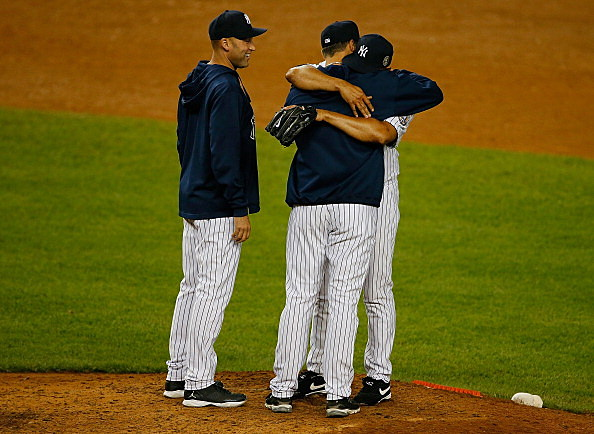 Mariano Rivera is hugged by Andy Pettitte #46 and Derek Jeter #2 as he is pulled the game against the Tampa Bay Rays at Yankee Stadium