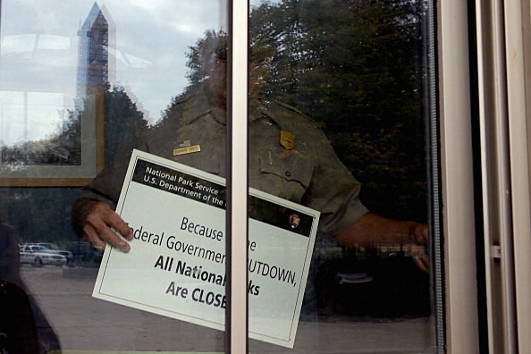 U.S. Park Service employee puts a closed sign in the window of the World War II Memorial ticket office on the National Mall