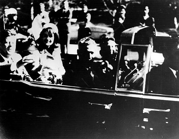 President John F. Kennedy (1917 - 1963) and his wife Jacqueline Kennedy ride with secret agents in an open car motorcade shortly before the president was assassinated in Dallas, Texas, November 22, 1963.