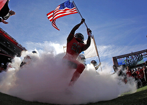 Johnathan Aiken #26 of the Rutgers Scarlet Knights carries the American flag out as he leads his team onto the field before the start of their game against the Cincinnati