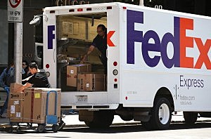 FedEx workers unload packages from a delivery truck