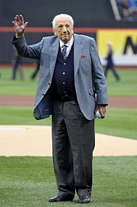 Ralph Kiner throws waves to the fans prior to throwing out the ceremonial first pitch to first base coach Mookie Wilson #1 of the New York Mets prior to the Mets playing against the Washington Nationals during the Mets' Home Opener at Citi Field on April 8, 2011