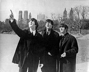 John Lennon (1940 - 1980), Paul McCartney and Ringo Starr, from left to right, enjoy a few moments away from the screaming fans when police smuggled them out of the side door of their hotel for a visit to New York's Central Park.