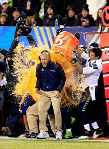 Tight end Zach Miller #86 and quarterback Russell Wilson #3 of the Seattle Seahawks dump Gatorade on head coach Pete Carroll