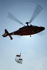 An aviation maintenance technician from Coast Guard Air Station Atlantic City, N.J., operates a rescue basket deployed from an MH-65 Dolphin helicopter during training off the coast of Atlantic City, N.J., Friday, Aug. 2, 2013. Helicopter crews train with the rescue basket to ensure proficiency during an actual emergency. U.S. Coast Guard photo by Petty Officer 3rd Class Cynthia Oldham