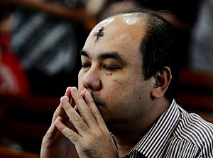 An Indonesian Catholic man prays during the Ash Wednesday ceremony at Roh Kudus Church in Surabaya, Indonesia