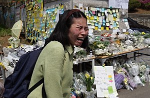 A woman weeps as she read messages wishing for the safe return of missing passengers of sunken passengers ship at Danwon high school in Ansan, South Korea