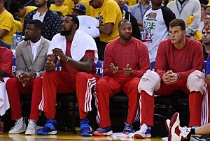 Los Angeles Clippers players sit on the bench wearing their warm-up tops inside out against the Golden State Warriors