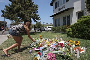 A woman places flowers on the lawn of the Alpha Phi sorority house May 25, 2014 in Isla Vista, California.