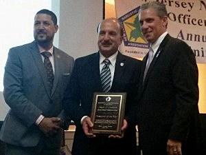 NJNEOA Awards Committee members Capt. Felix Pacheco (Grey Suit) & Capt. Bob DiGenova present Jospeh Coronato (Center) with Prosecutor of the Year Award