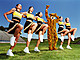 Cheerleaders dancing arm and arm in formation, tiger mascot in middle