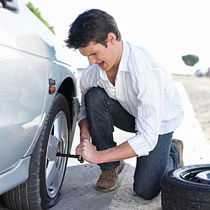 Man changing flat tire in car